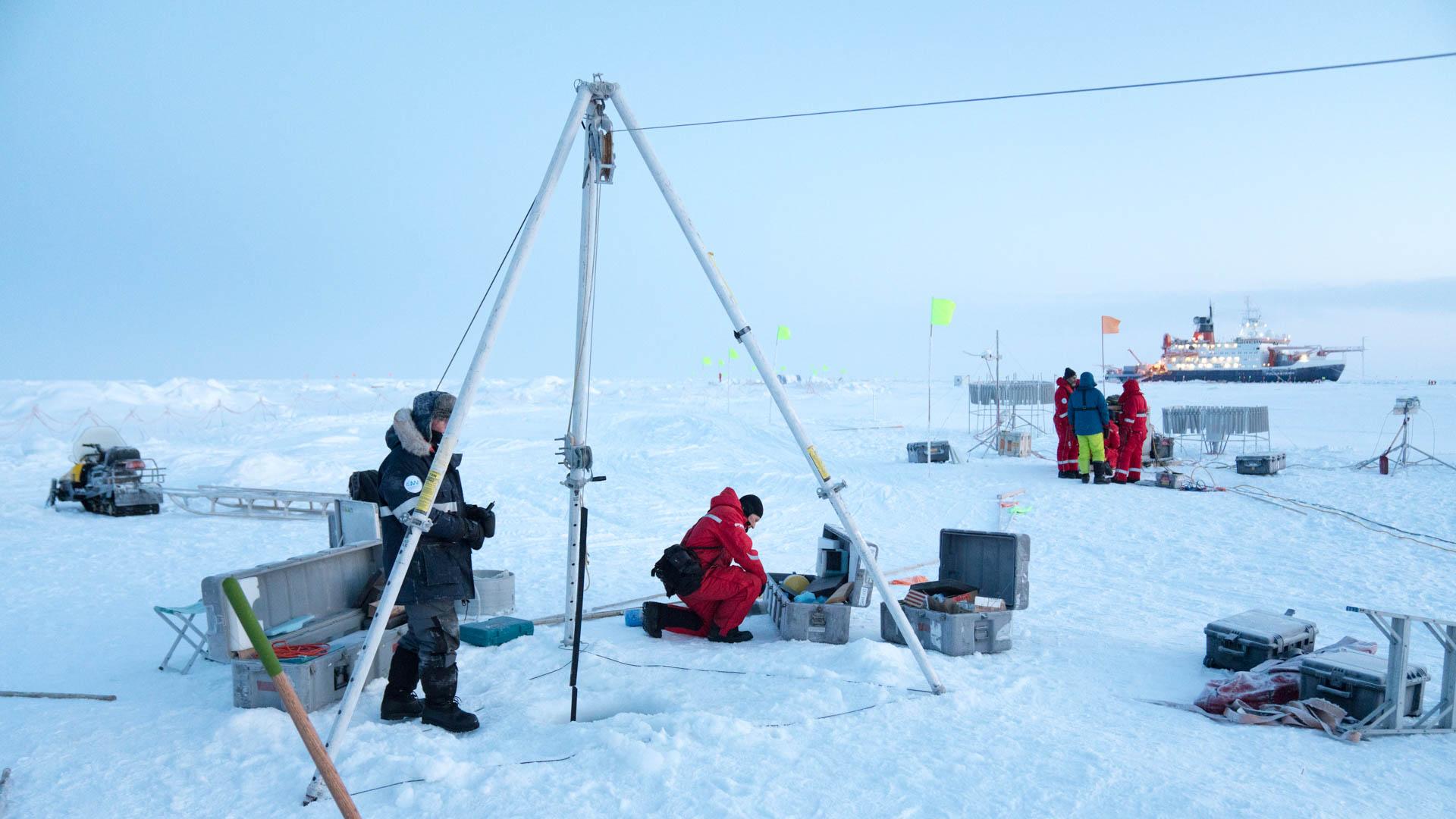 wissenschaftler-bauen-ein-dreibein-zum-versenken-einer-messboje-in-met-city-waehrend-der-mosaic-expedition-im-hintergrund-das-forschungsschiff-polarstern.jpg